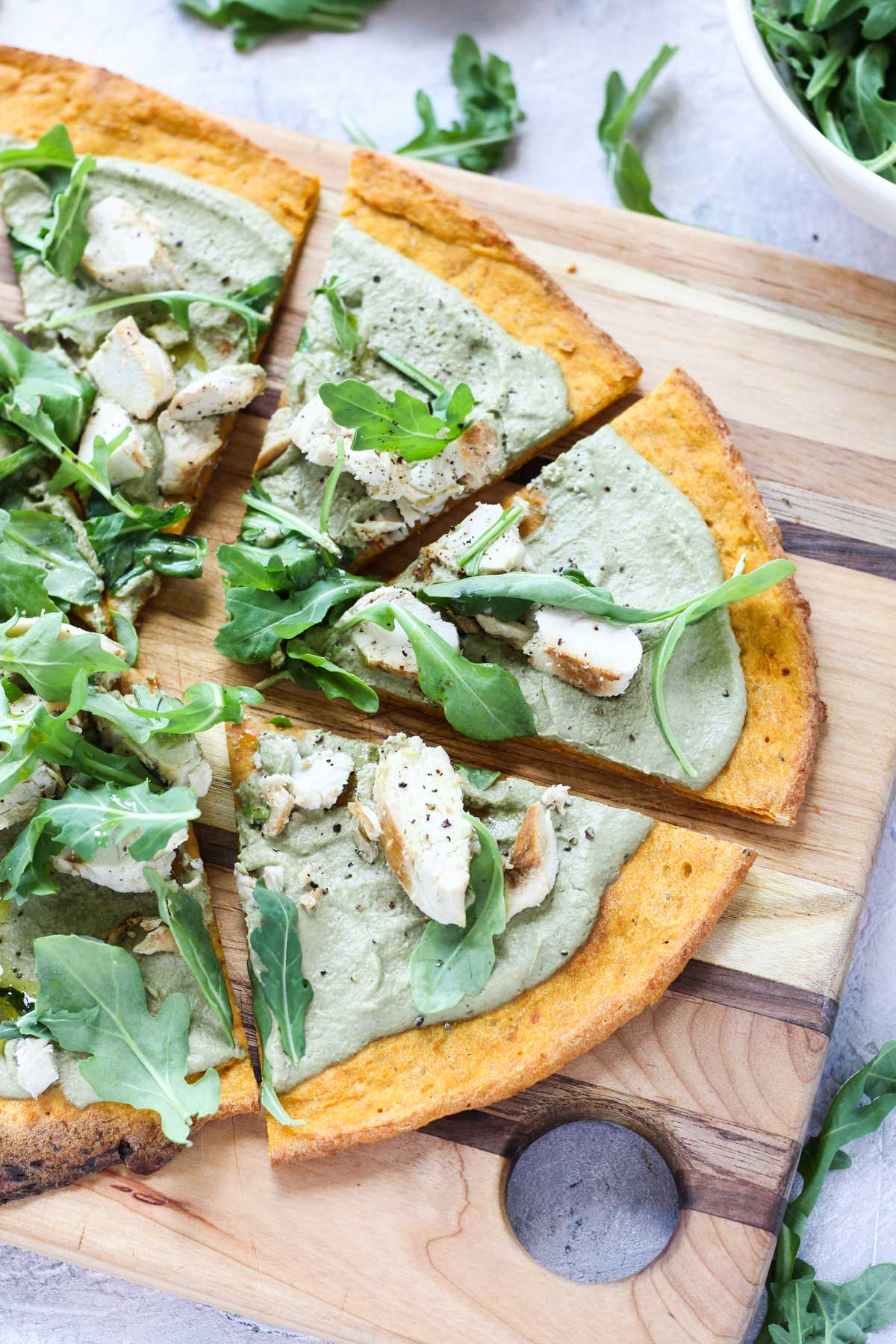 Pesto pizza on cutting board.
