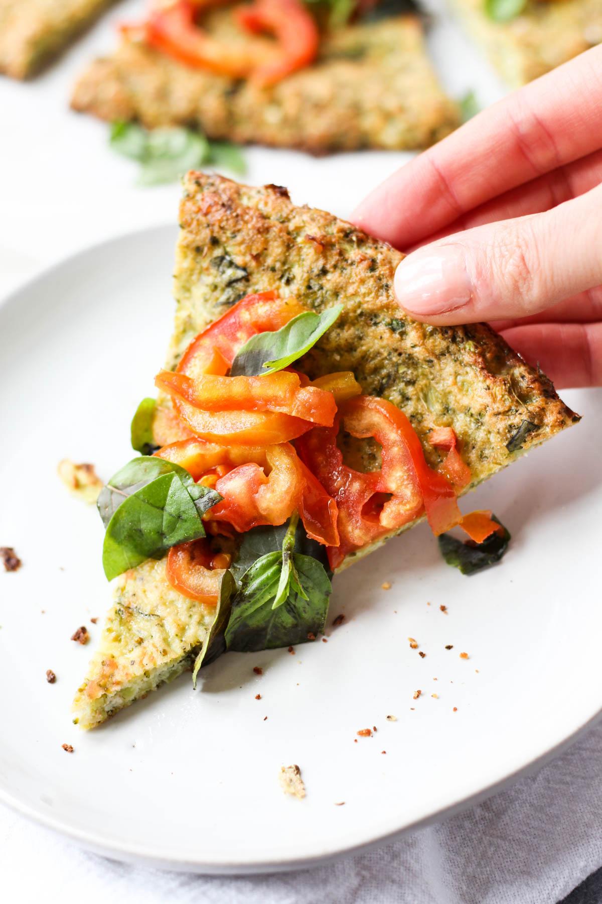 Hand holding slice of broccoli crust pizza.