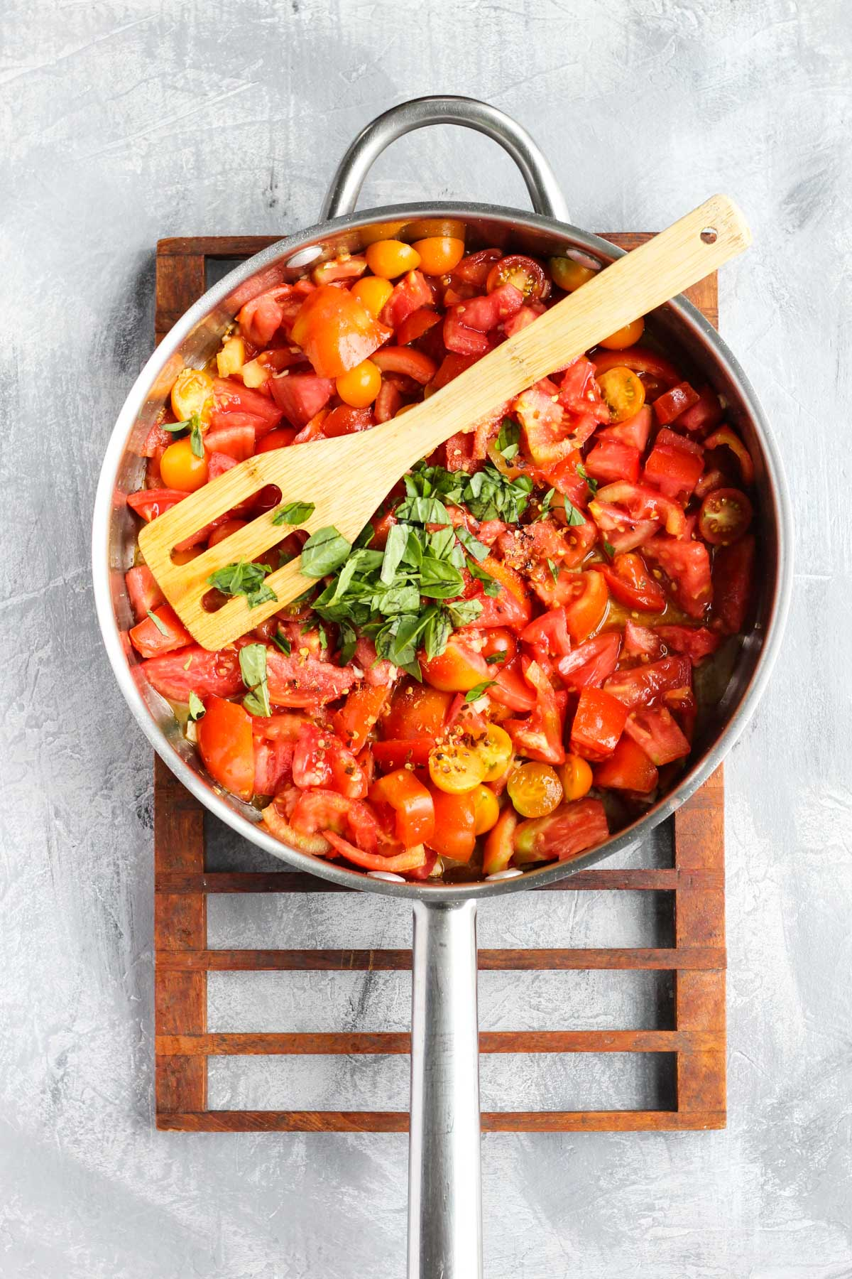 Large pan with tomatoes, herbs, and spices.