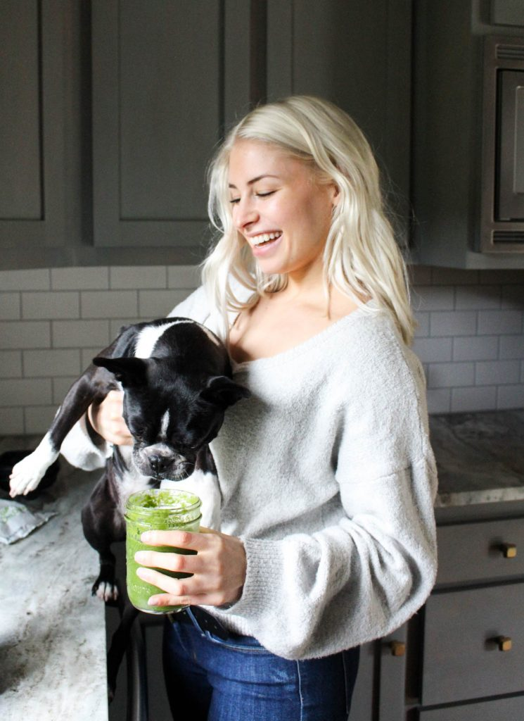 Girl laughing holding dog and green smoothie.
