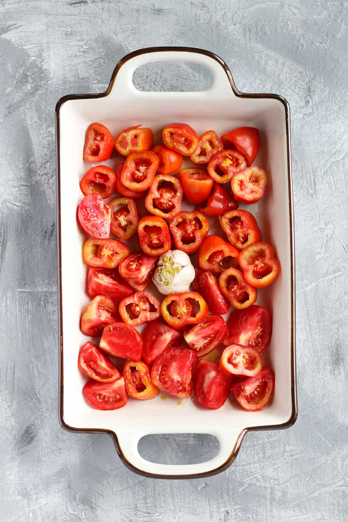 Tomatoes and garlic in a roasting pan.