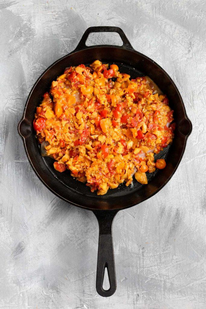 Chicken in cast iron skillet with peach salsa.