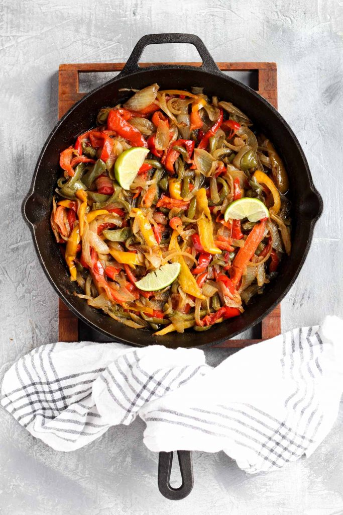 Overhead shot of cooked peppers and onions in pan.