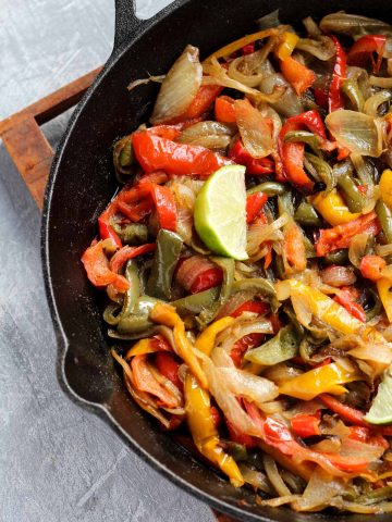 Close up picture of peppers and onions in cast iron skillet.