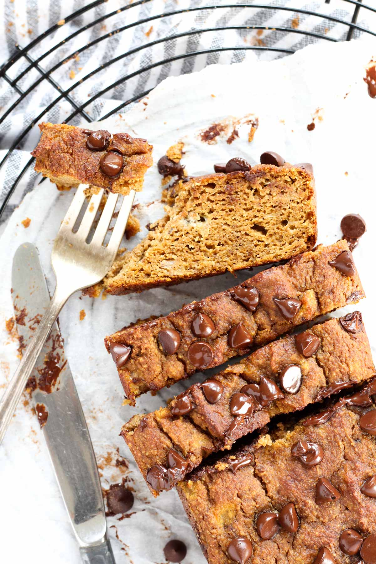 Overhead shot of pumpkin banana bread cut into thick slices with a fork on the side.